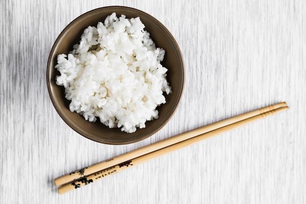 Palillos de madera cerca de un tazón con arroz