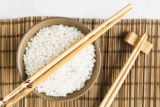 Palillos de madera y taza con arroz blanco en estera de bambú