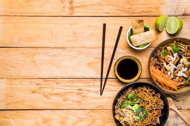 Palillos con rollitos de primavera; fideos y salsas con palillos en mesa de madera.