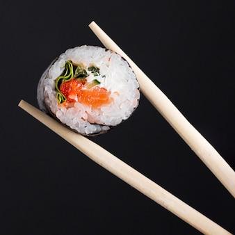 Palillos con rollo de sushi