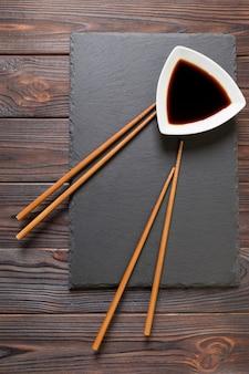 Palillos y salsa de soja sobre placa de piedra negra.