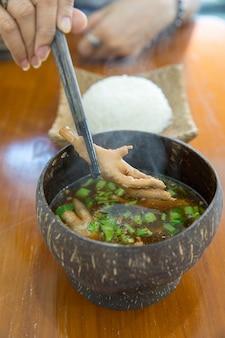 Los palillos con sopa de pollo al pie.