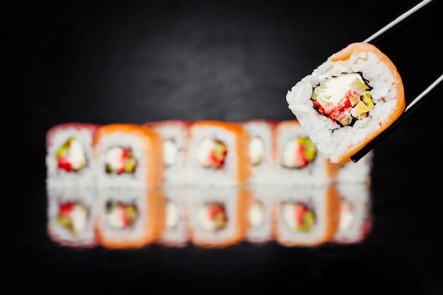 Palillos sosteniendo rollo de sushi filadelfia hecho de salmón, atún, pepino, nori