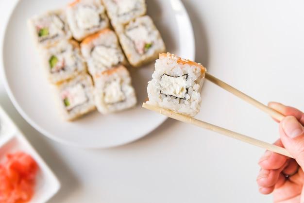 Palillos sosteniendo un rollo de sushi