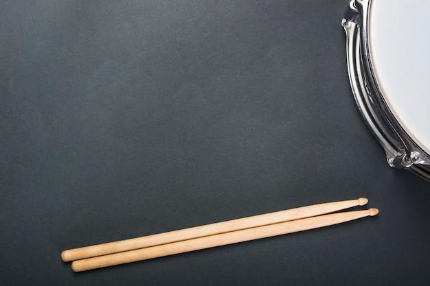 Palillos y tambor de madera sobre fondo negro