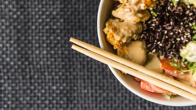 Palillos en un tazón de arroz con espacio de copia