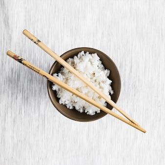 Palillos en un tazón con arroz