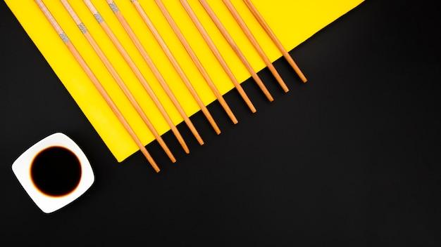 Palillos con tazón de salsa de soja sobre un fondo amarillo y negro