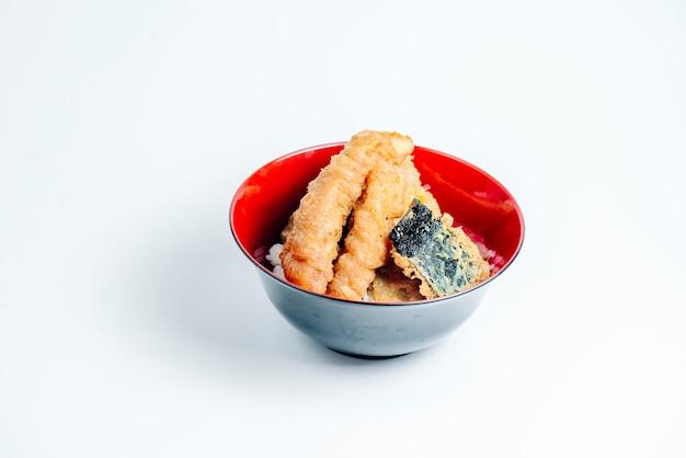 Palito de pescado frito crujiente y trozo de pescado sobre arroz en fondo blanco.