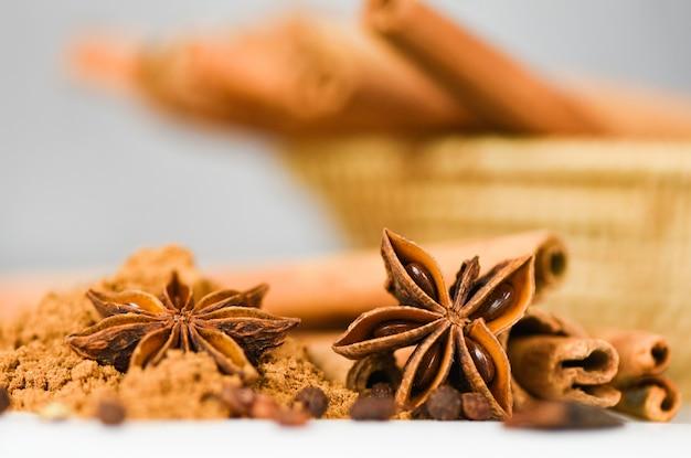 Palitos de canela y anís estrellado sobre canela en polvo hierbas y especias en blanco