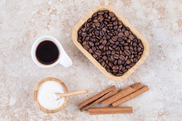 Palitos de canela, granos de café, azúcar y una taza de café.