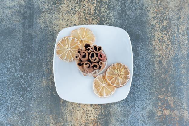 Palitos de canela y limones en rodajas en un plato blanco.