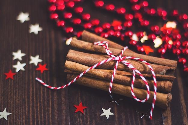 Palitos de canela navideños atados con una cuerda en una mesa festiva de madera