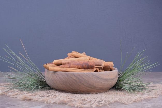 Palitos de canela en una taza de madera con rama de roble alrededor