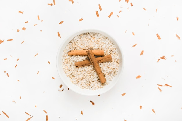 Palitos de canela en el tazón de arroz crudo sobre fondo blanco