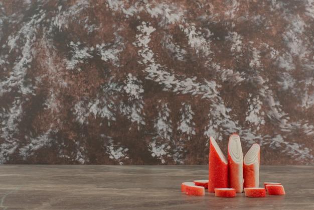 Palitos de cangrejo sabroso sobre fondo de mármol.