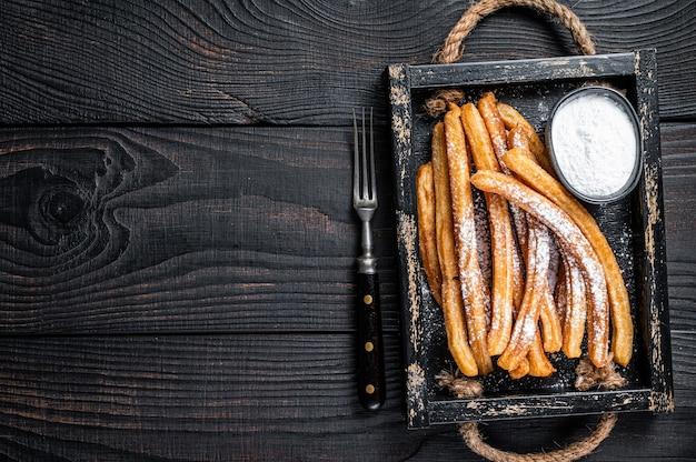 Palitos de churros fritos con azúcar en polvo en bandeja de madera