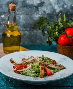 Palitos de cordero a la parrilla con lechuga, rodajas de tomate, queso en salsa
