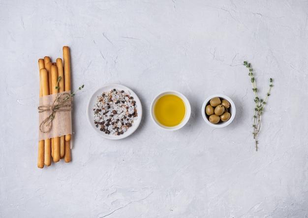 Palitos grissini italianos pan con sal, oli de oliva y tiroides en mesa beton blanca