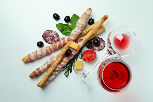 Palitos de grissini con tocino, aperitivos y vino sobre fondo blanco.