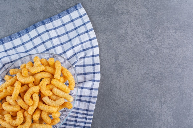 Palitos de maíz dulce en un recipiente sobre un paño de cocina, sobre la superficie de mármol