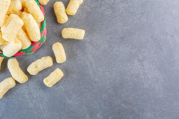 Palitos de maíz dulce en un recipiente, sobre la superficie de mármol