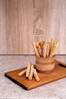 Palitos de pan crujiente con semillas de sésamo y pan de salvado sobre una tabla de madera.