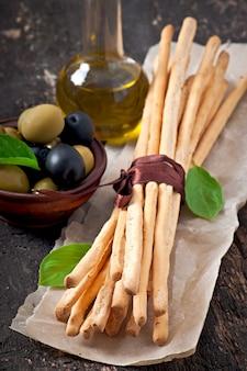 Palitos de pan grissini con jamón, aceitunas, albahaca sobre madera vieja