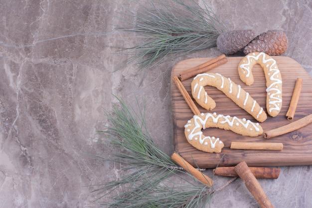 Palitos de pan de jengibre sobre una tabla de madera con canela alrededor