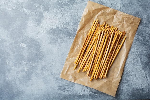 Palitos de pan salado o palitos de pretzel salados crujientes largos sobre papel de pergamino sobre piedra gris vieja o una mesa de hormigón. vista superior.