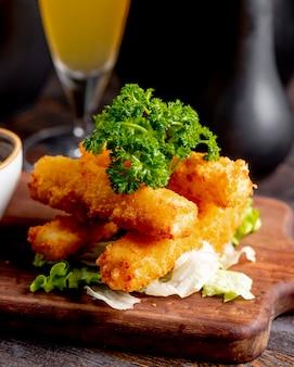 Palitos de pollo frito servidos con lechuga y verduras