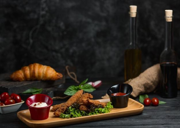 Palitos de pollo con vinagre balsámico y aceite de oliva.