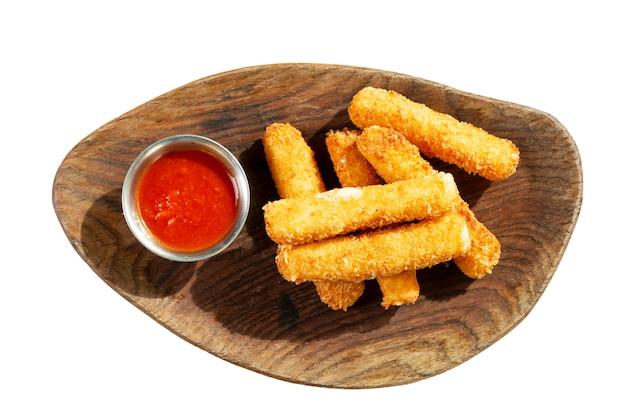 Palitos de queso a la plancha con salsa roja, servidos en una tabla de madera