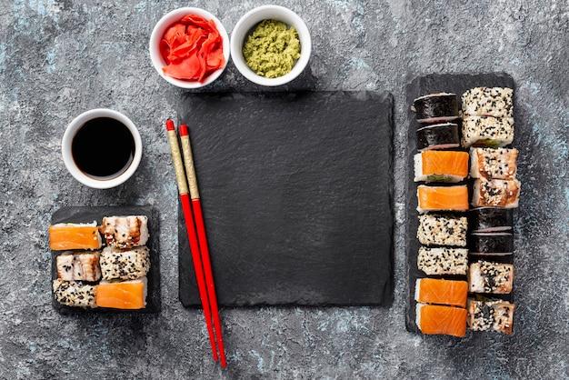 Palitos de sushi maki planos y planos con salsa de soja y pizarra en blanco