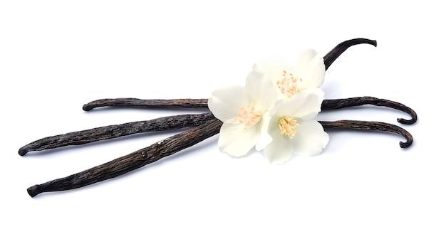 Palitos de vainilla con flores sobre blancos.