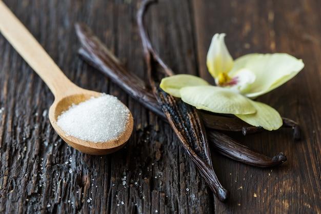 Palitos de vainilla secos, azúcar y orquídea de vainilla en la mesa de madera. de cerca.
