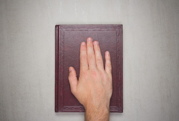 La palma de un hombre sobre un libro, un juramento sobre la biblia.