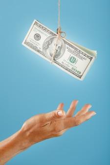 La palma llega al dinero suspendido de una cuerda, en un azul.