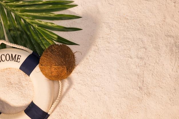 Palmera con hoja de coco y salvavidas en la arena.