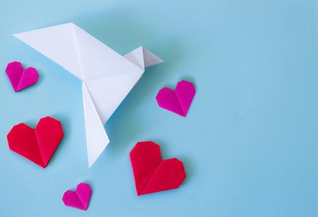 Paloma blanca de papel con corazones rojos y rosas