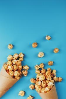 Palomitas de caramelo en un sobre de papel sobre un fondo azul.