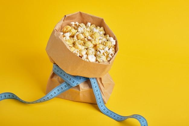 Palomitas de maíz en una bolsa de papel con cinta métrica azul sobre fondo amarillo