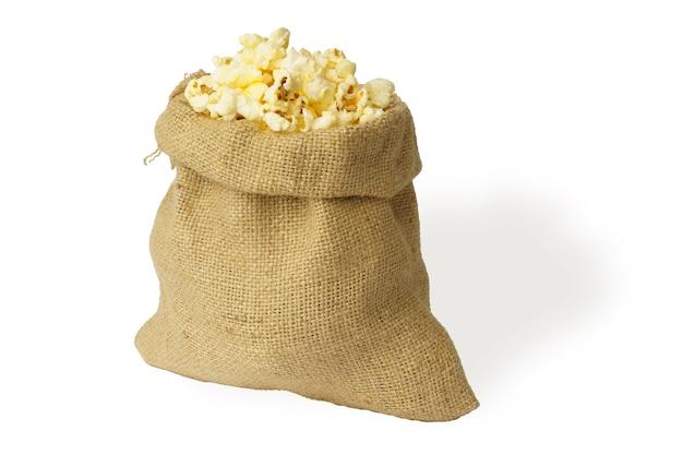 Palomitas de maíz en una bolsa de saco aislado en blanco.