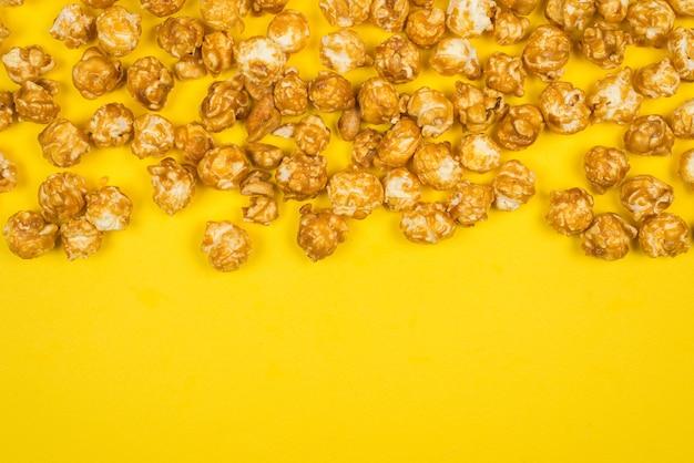 Palomitas de maíz de caramelo sobre fondo amarillo. copie el espacio.