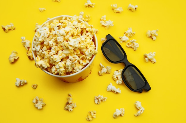Palomitas de maíz en un cuenco y gafas 3d en amarillo