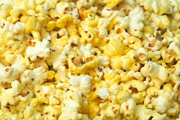 Palomitas de maíz en un fondo coloreado. concepto de comida mínima. entretenimiento, contenido de cine y video. concepto de estética años 80 y 90