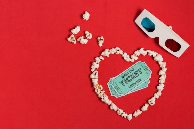 Palomitas de maíz en forma de corazón con gafas y entradas