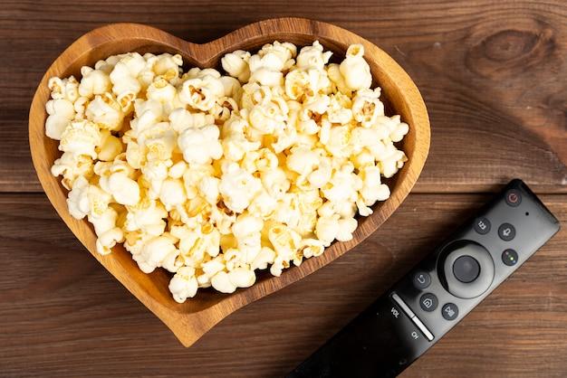 Palomitas de maíz en forma de corazón en un tazón de madera y un control remoto de televisión en una mesa de madera