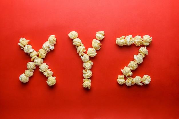 Palomitas de maíz formando la letra x, y, z sobre fondo rojo