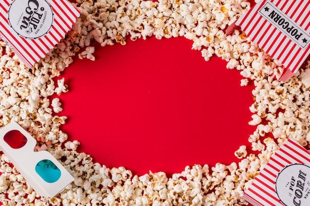 Palomitas de maíz y gafas 3d con espacio de copia para escribir el texto sobre fondo rojo